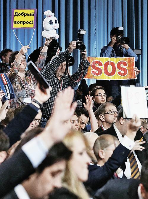 Чтобы получить возможность задать вопрос, журналисты старались как могли. Одни поднимали руки, другие - заранее написанные плакаты. А кто-то решил, что внимание президента непременно привлечет плюшевый заяц. Фото: ТАСС