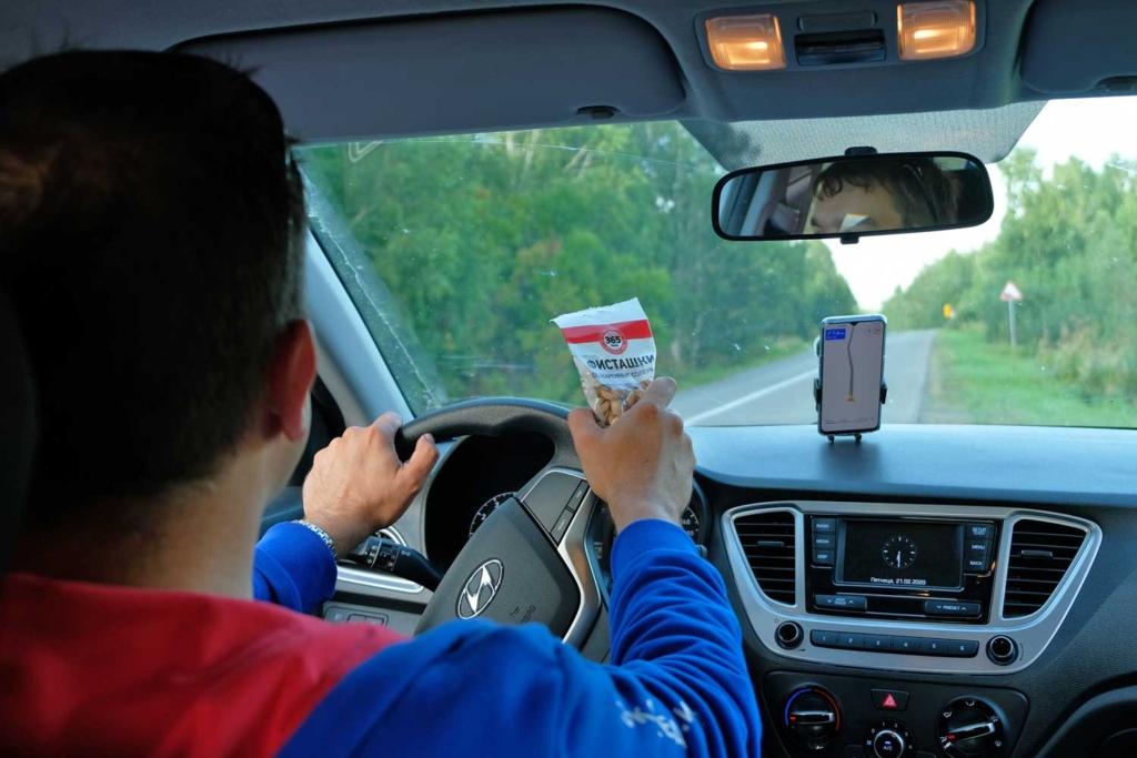 мужчина за рулем ест фисташки