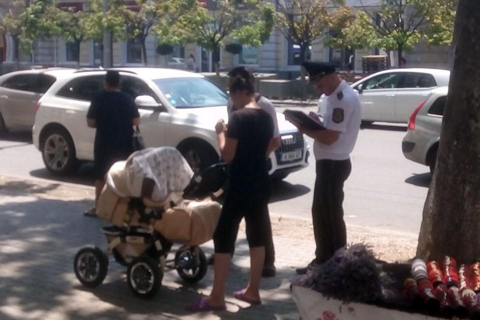 Полицейский и семейная пара с коляской вышли из людского потока для составления протокола