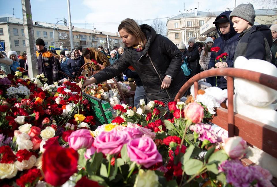 """Люди несут цветы к зданию сгоревшего ТЦ """"Зимняя вишня"""" в Кемерово"""