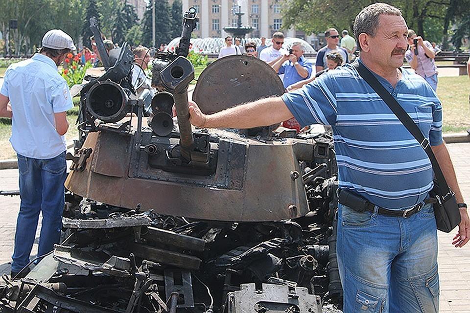 Жители Донбасса на фоне уничтоженной украинской военной техники.