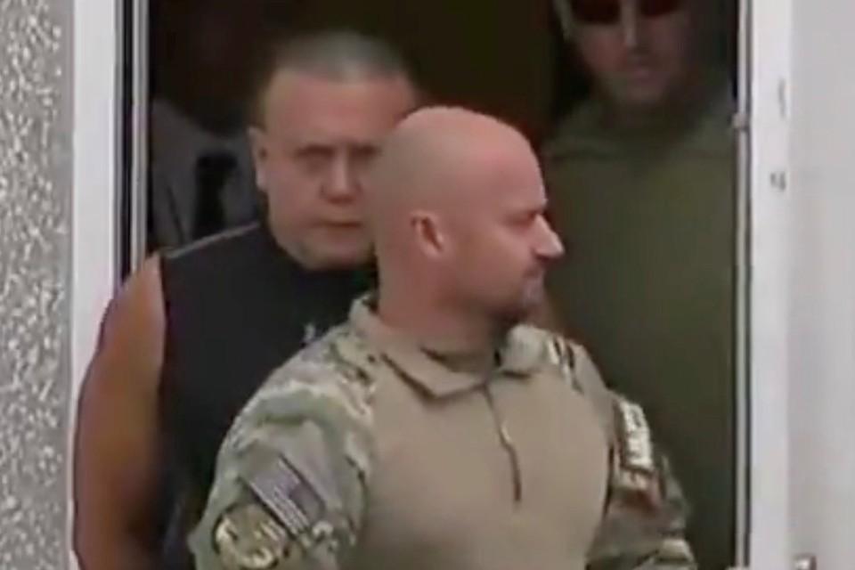 Подозреваемый в рассылке взрывных устройств, американец Сэйзар Сэйак - младший (позади мужчины в военной форме)