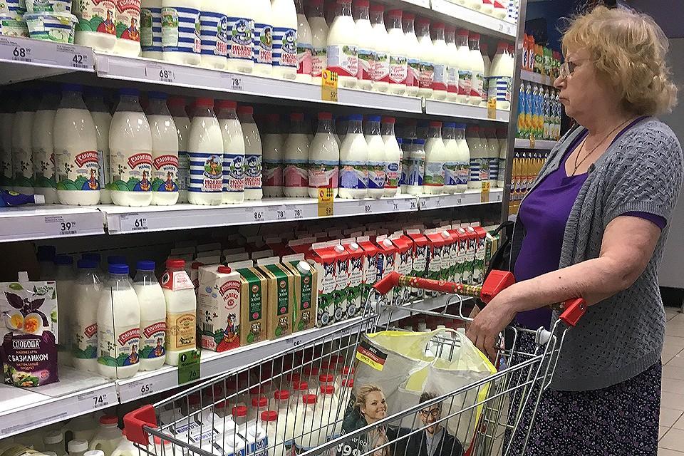 У полки с молочными продуктами в супермаркете.