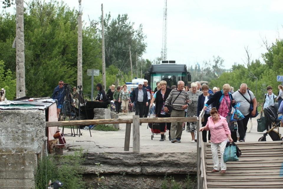 Пожилые люди с трудом преодолевают «полосу препятствий» из деревянных лестниц, установленных на разрушенном мосту через реку Северский Донец. Фото: lug-info.com