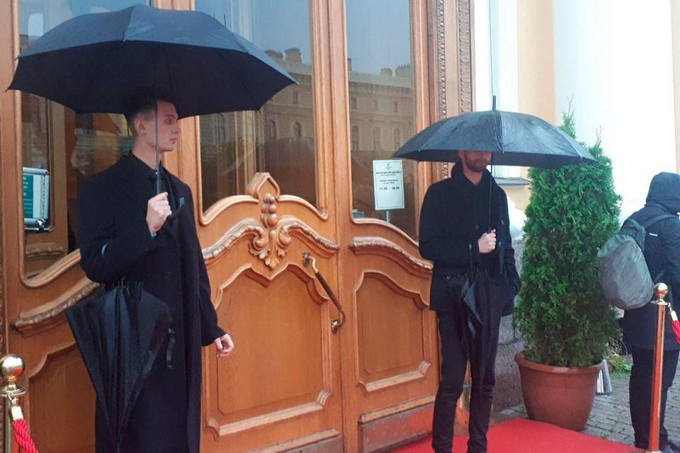 Перед Юсуповским дворцом гостей торжества в честь свадьбы Бондарчука и Андреевой встречают мужчины с черными зонтами - в Петербурге дождь.