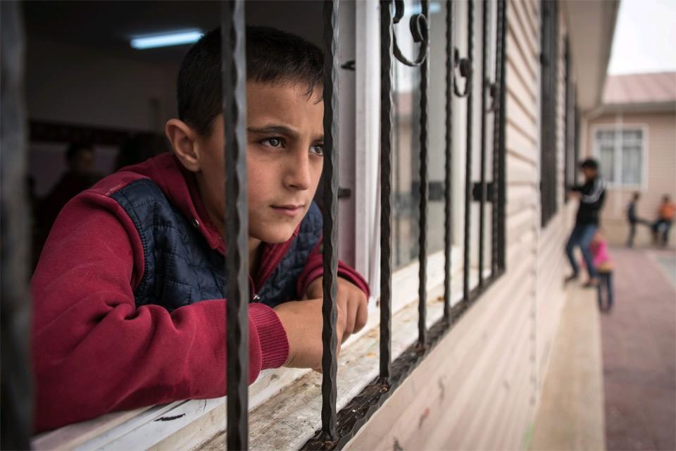 Сирийский подросток выглядывает из окна лагеря беженцев, Турция.