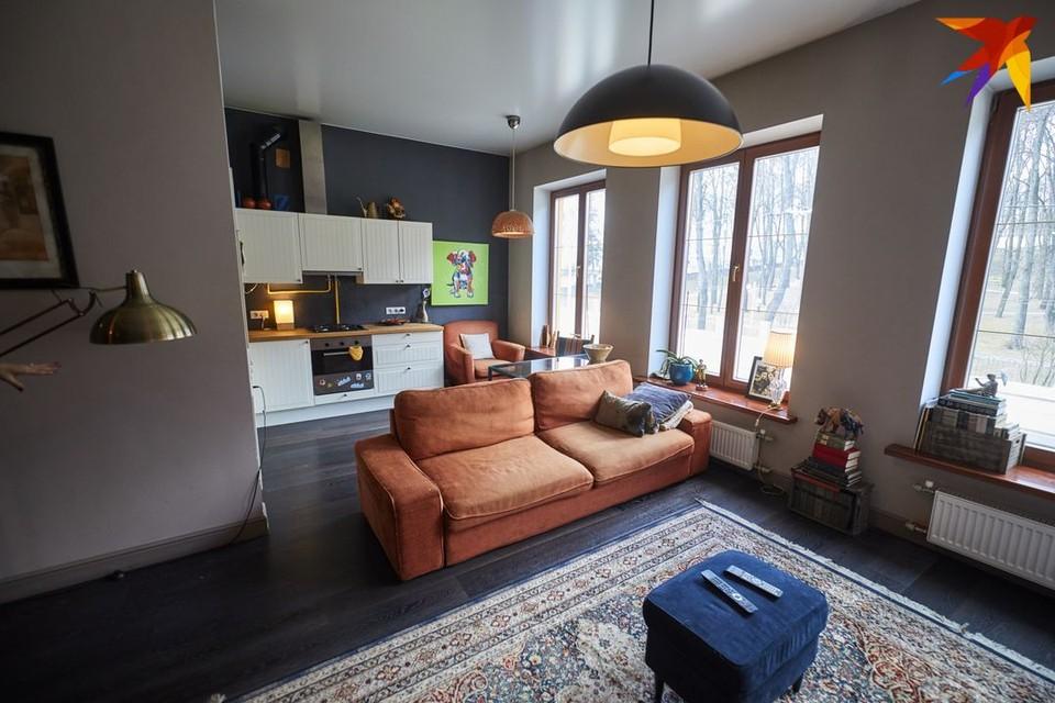 На окнах нет штор и тюли. А черный пол идеально сочетается с терракотовым диваном.