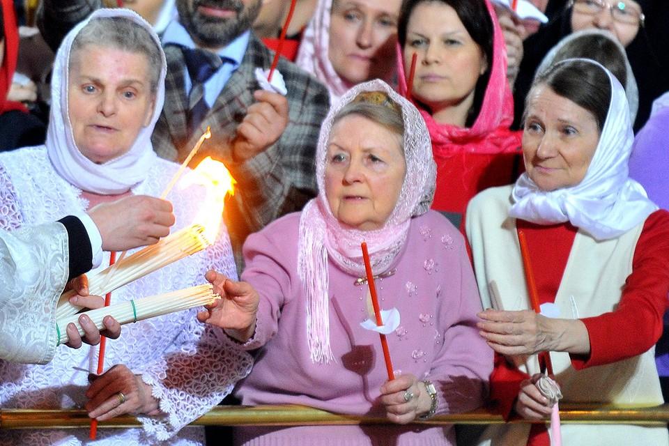 Верующие и Благодатный огонь во время службы в Храме Христа Спасителя.