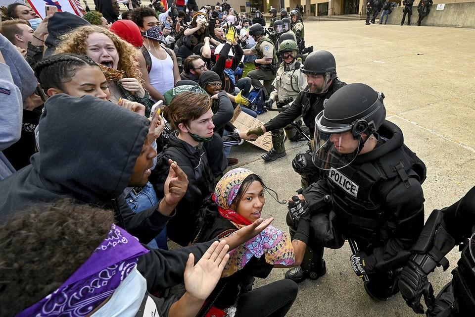 Полицейские опустились на одно колено перед разгневанной толпой молодежи в городе Спокан, штат Вашингтон, США.