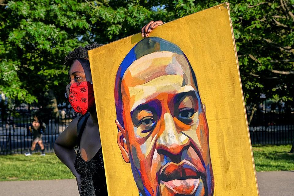 Участница американского протеста с портретом Флойда.