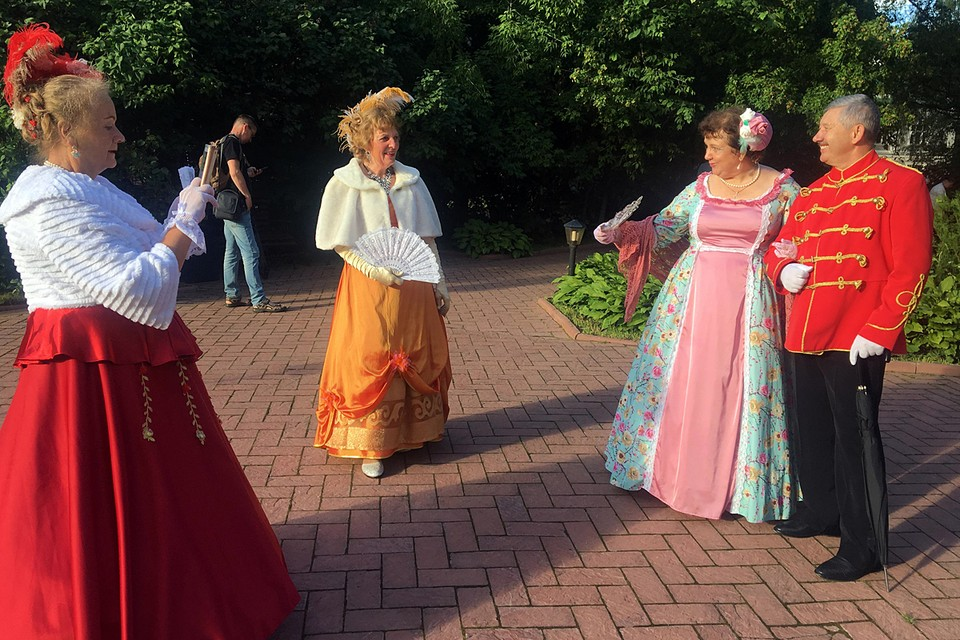 На улице прекрасно и солнечно. Антуражные дамы в шляпах, фижмах и турнюрах ведут светские беседы