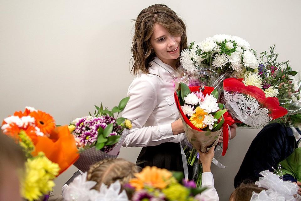 Дети дарят цветы учительнице в День знаний 1 сентября.