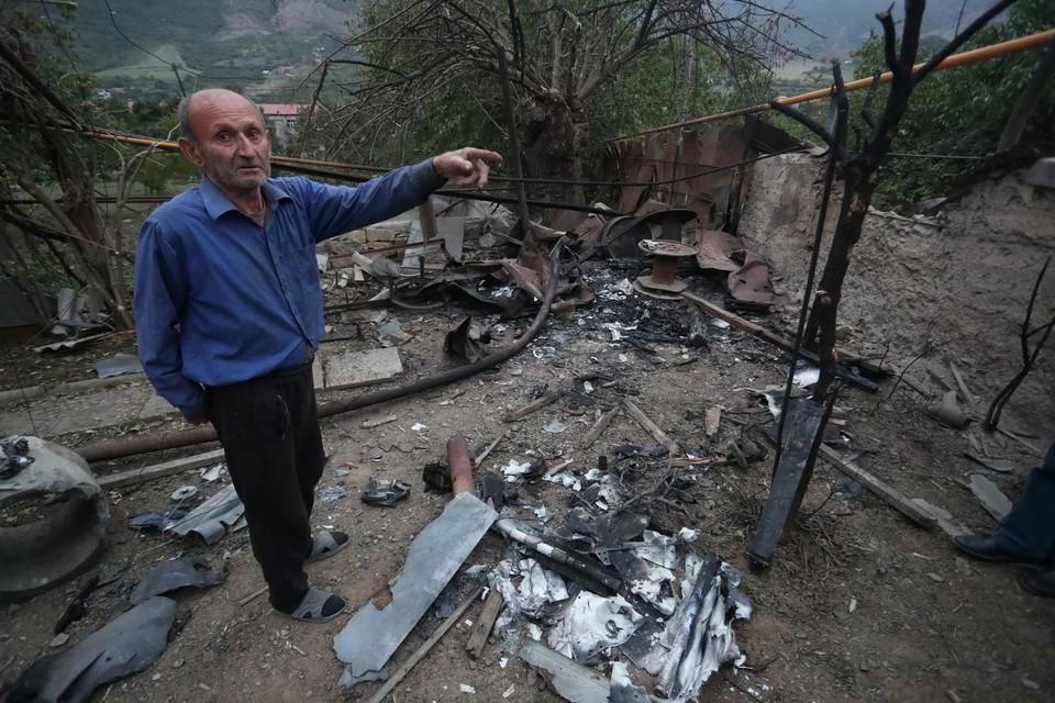 Житель города Гадрут показывает на разрушения после обстрела.