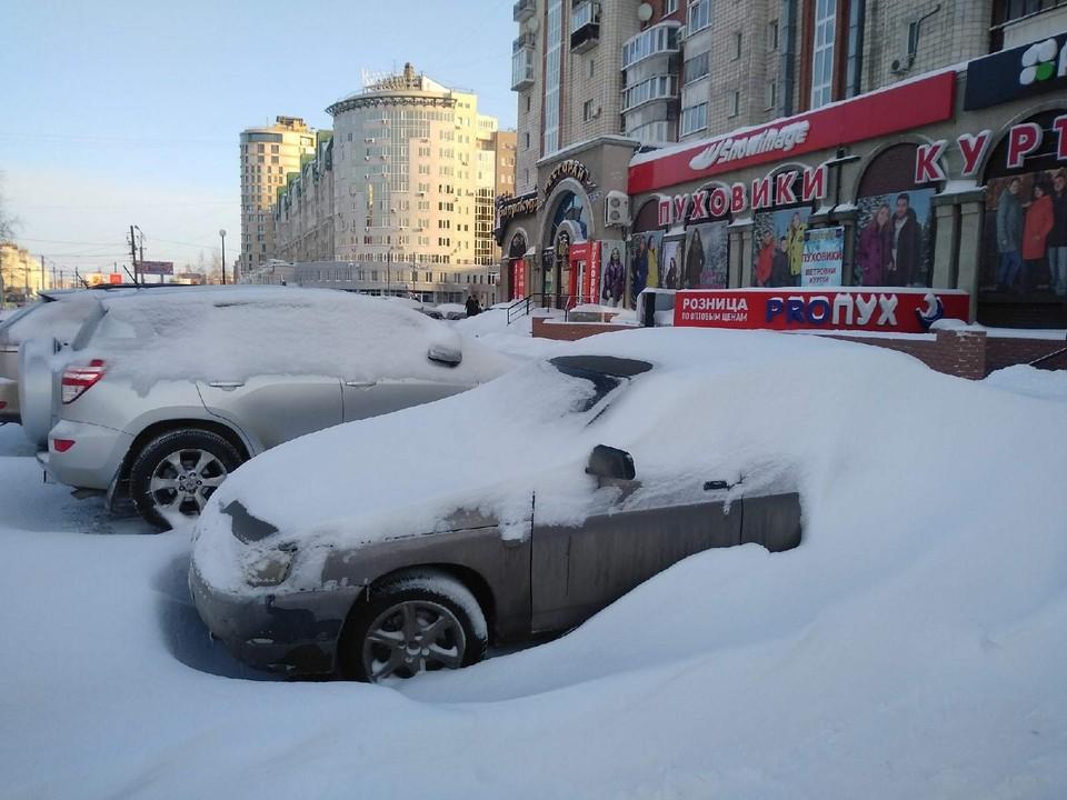 Некоторые машины на парковке накрыло огромным слоем снега.