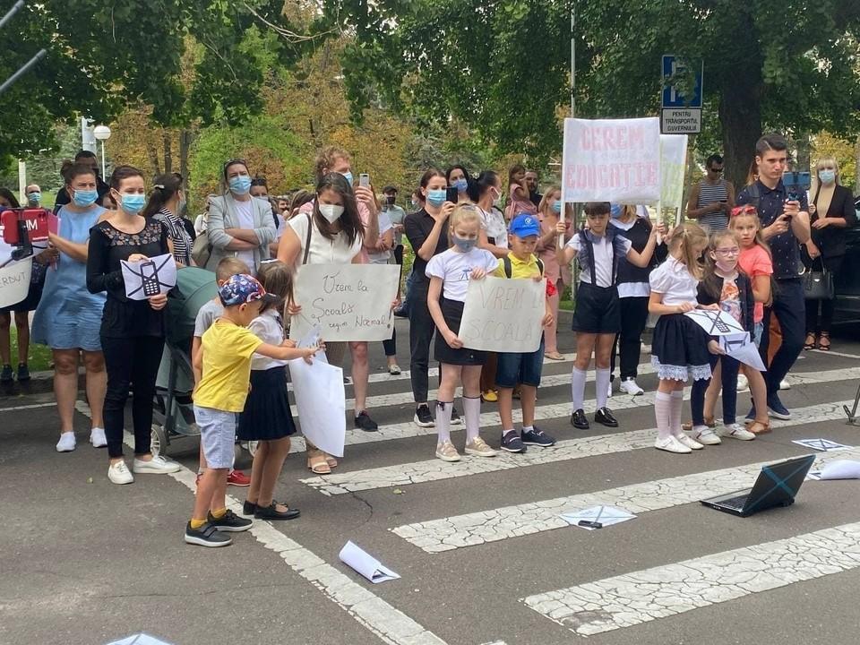 Десятки родителей и учеников протестуют у правительства против наложенных ограничений.