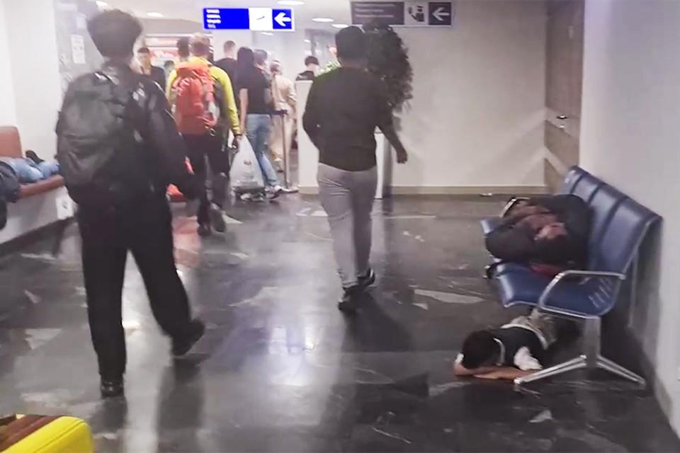 В транзитной зоне минского аэропорта застряли десятки мигрантов – они спят на полу. Кадр видео sputnik.by.
