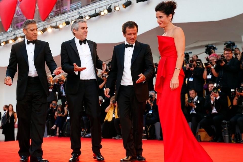 В Венеции открылся кинофестиваль/ На красной дорожке: актер Джордж Клуни, режиссер Альфонсо Куарон, продюсер Дэвид Хейман приветствуют Сандру Буллок