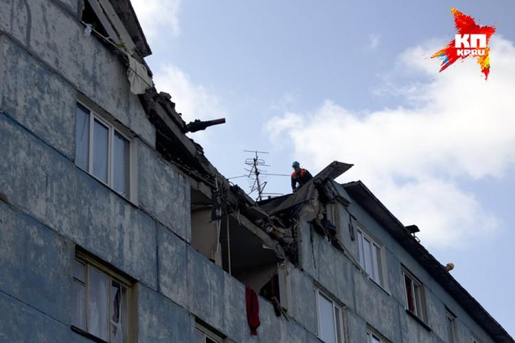 Спасатель заглядывает в разрушенную квартиру через провал в крыше дома на улице Александра Невского