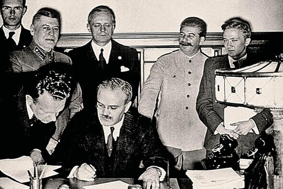 Молотов подписывает пакт, прямо за его спиной Риббентроп, справа от которого- Сталин.
