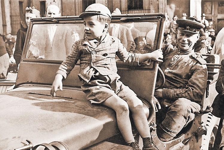 А это фото подписано так: «Мальчик в одной из освобожденных местностей с воином Красной Армии». Венгрия, 1 марта 1945 г.