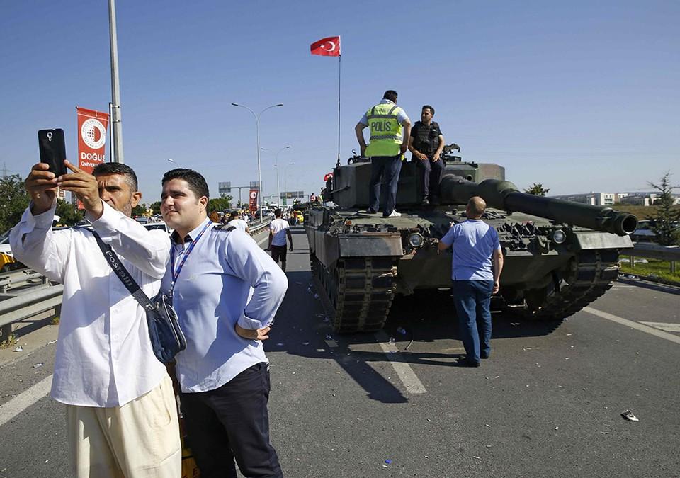 Турки фотографируются на фоне танка, оставленного путчистами у аэропорта Сабиха Гётчен в Стамбуле.