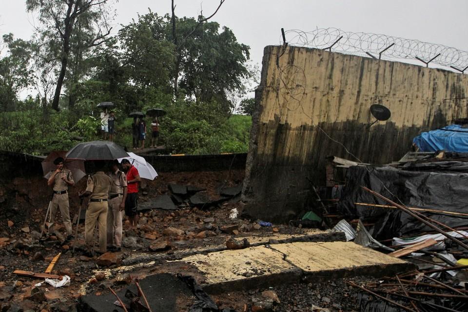 Полицейские у остатков стены, рухнувшей из-за ливней и оползней на трущобы в индийском Мумбаи.