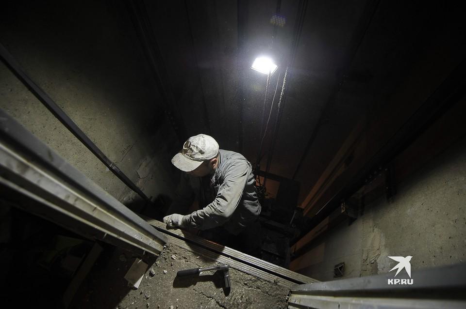 Рабочий во время замены лифта в подъезде жилого многоквартирного дома