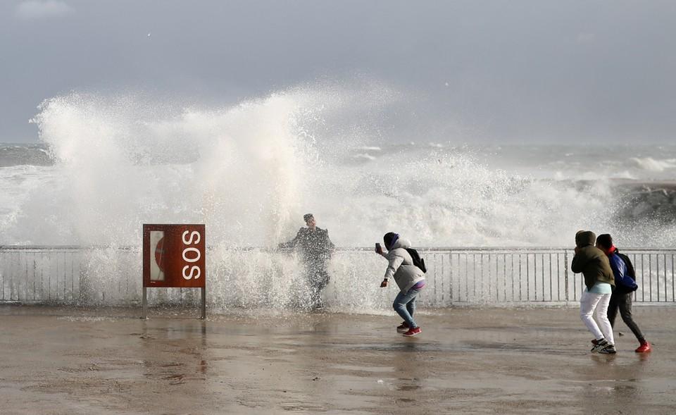 Туристы фотографируются во время сильных волн на одном из пляжей Испании.