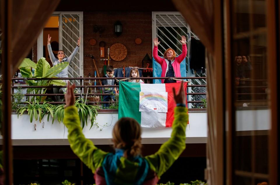 Итальянцы занимаются физическими упражнениями на балконе в очередной день национального карантина.