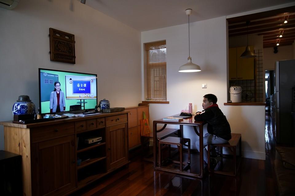 Шанхайский школьник смотрит передачу с курсом школьной программы.
