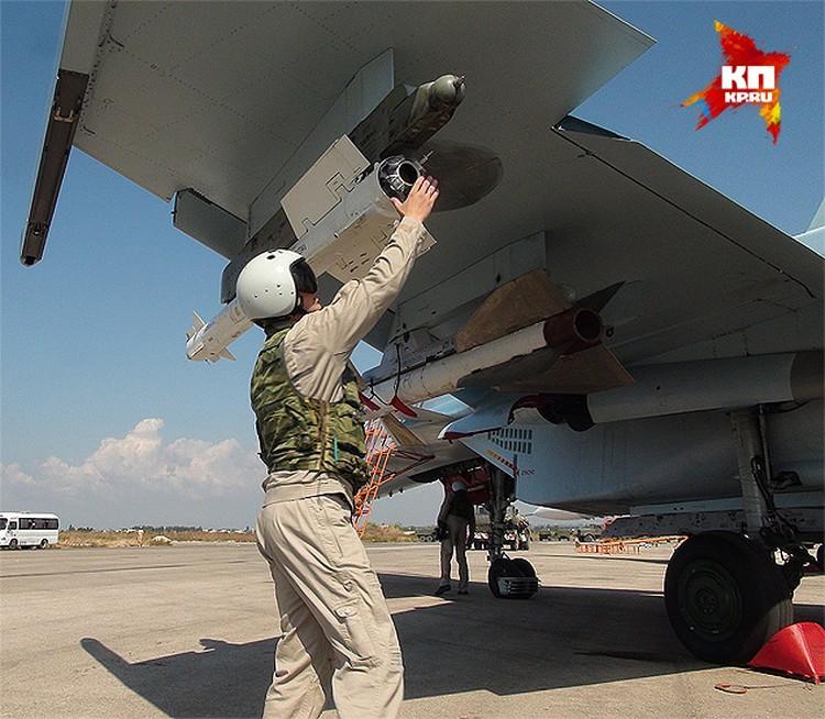 """Аэродром `Хмеймим`. Летчик боевой машины Су-30 осматривает сопло двигателя ракеты """"воздух-воздух""""."""