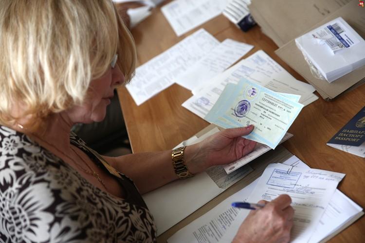 Сотрудница приемной комиссии скрупулезно записывает номера сертификатов.