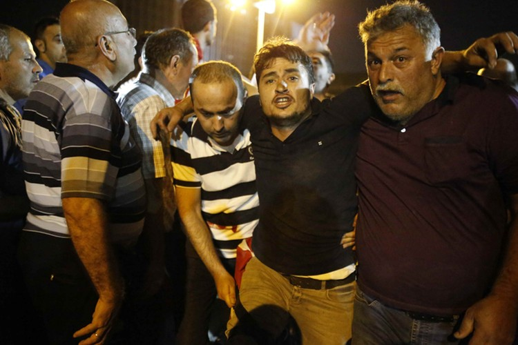 Люди помогают раненому в результате столкновений с военными мужчине на площади Таксим