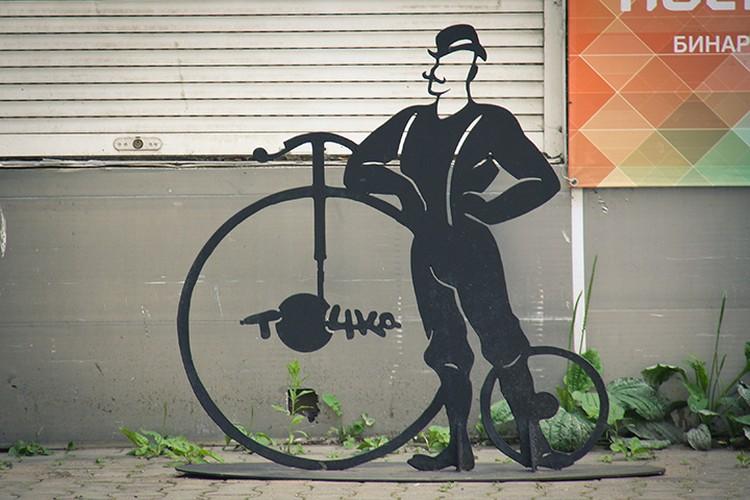 Прямо напротив арки возле магазина «Точка» еще один велосипед, только уже старинный, с большим передним колесом.