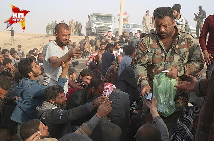Иракский офицер раздает сигареты.
