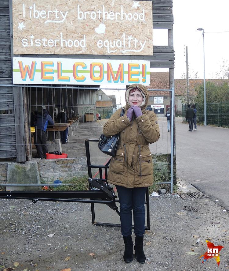 """Дарья Асламова в лагере беженцев во французском Дюнкерке. Надпись на плакате """"Добро пожаловать. Свобода, братство, сестринство, равенство"""""""