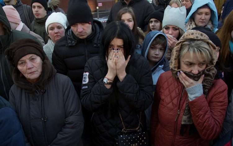 Люди перед зданием сгоревшего ТЦ. Пожар стал настоящей трагедией для всей страны