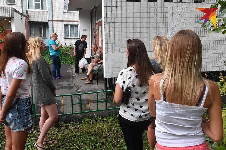 Соседи и подруги сестер у подъезда их дома.