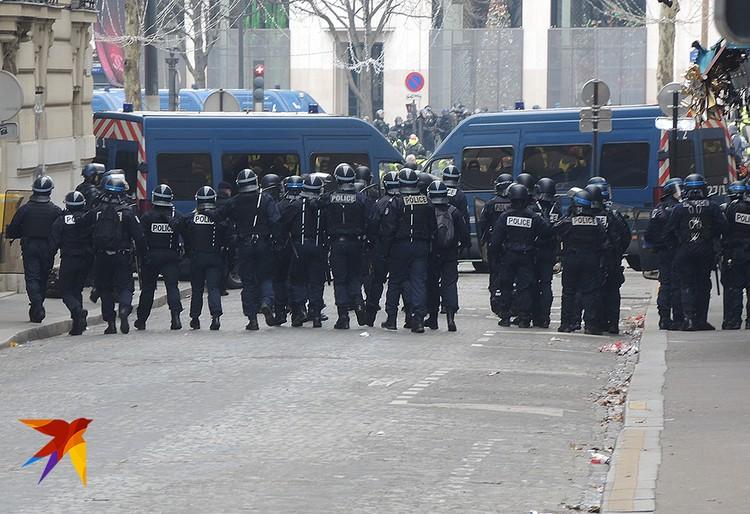 Цепь полицейских блокирует улицу.