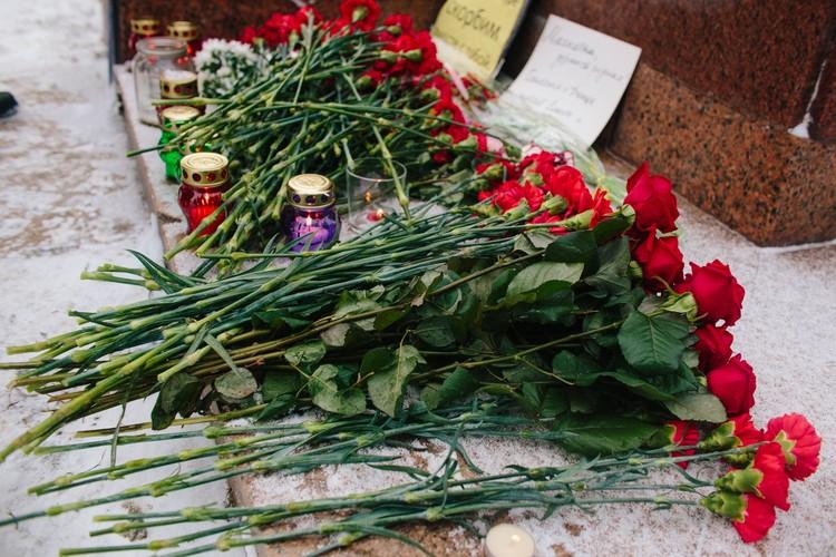 Люди несли к памятнику розы и гвоздики.