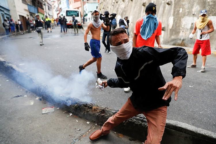 Участник уличных беспорядков метает заряд слезоточивого газа в полицейских.