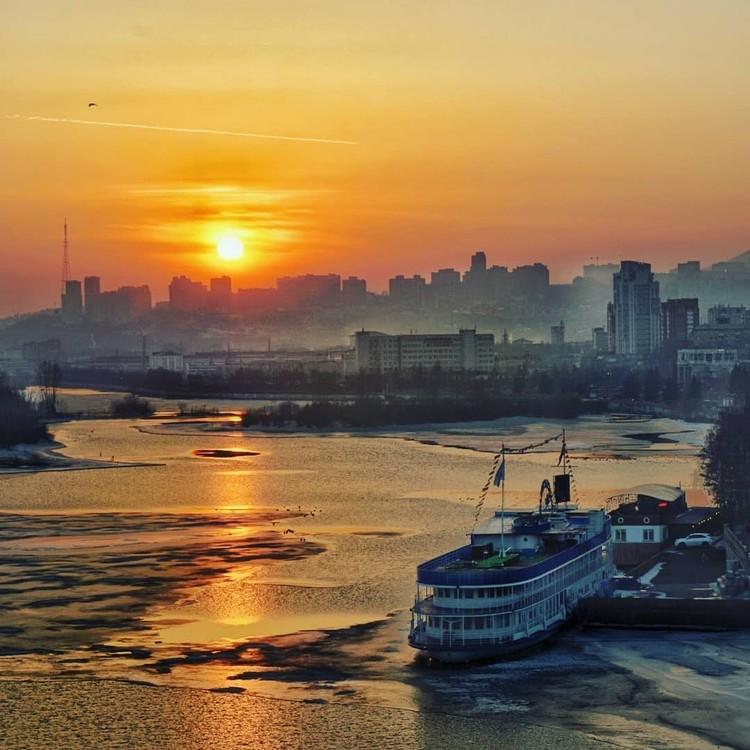 Потрясающее фото красноярского заката Стефано Ферро: Енисей словно море, корабль у пристани, вдали, над высотками, садится солнце. Фото: Follow Up Siberia
