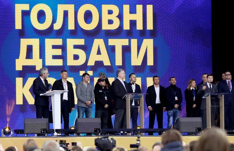 """Участники дебатов на сцене, установленной на стадионе """"Олимпийский"""" в Киеве."""