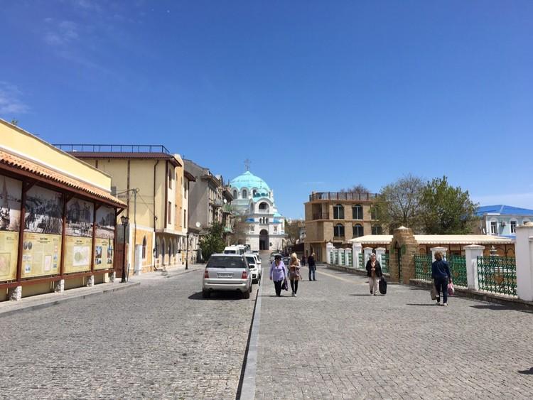 В центре Евпатории гуляют туристы и фотографируются на фоне достопримечательностей
