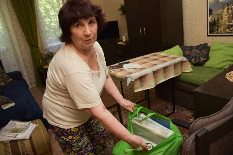 Софья Бабешко устала ждать переселения, но и в маневренный фонд съезжать не хочет. Женщина показывает сумку, в которой переписка с чиновниками.
