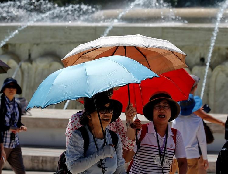 Туристы из Китая прячутся от солнца на одной из площадей столицы Мальты.
