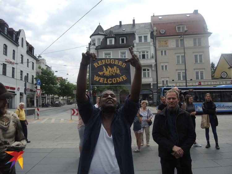 «Добро пожаловать, беженцы» - плакат с этой надписью держит довольный смуглокожий мигрант в Мюнхене. Многие немцы его радость не разделяют.