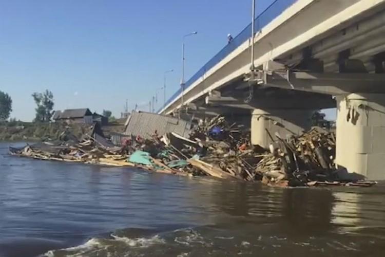 Смытые течением дома прибило к этому мосту через реку Ия. Фото: ГУ МЧС России