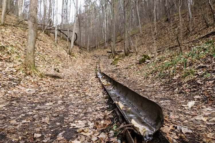 Вдоль тропы по вросшему в землю желобу стекает прозрачная вода.