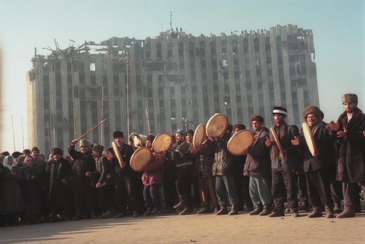 Чеченцы празднуют победу после провала штурма Грозного. Позади - все, что осталось от Дома правительства республики.